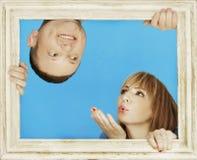 Couples derrière le cadre en bois sur le fond de bleu de ciel Photos stock