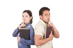 Couples des étudiants attirants heureux gais tenant le livre Photo stock