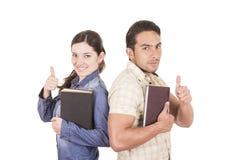 Couples des étudiants attirants heureux gais tenant le livre Images stock