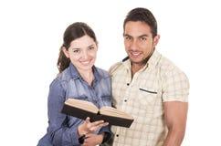 Couples des étudiants attirants heureux gais tenant le livre Photographie stock