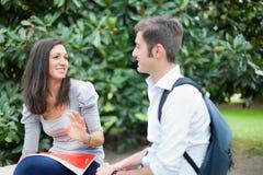 Couples des étudiants parlant extérieurs Photographie stock