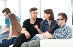 Couples des étudiants s'asseyant sur un sofa avec des amis dedans Images libres de droits