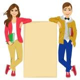 Couples des étudiants universitaires se penchant contre un conseil vide Photos stock