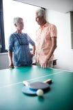 Couples des aînés agissant l'un sur l'autre derrière une table de ping-pong Images stock
