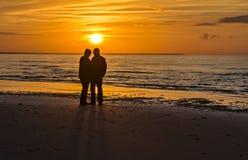 Couples des aînés heureux à une plage de la mer baltique pendant le coucher du soleil Photographie stock libre de droits