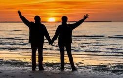 Couples des aînés heureux à une plage de la mer baltique pendant le coucher du soleil Photo stock