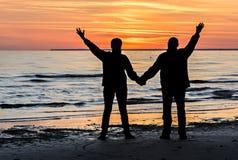 Couples des aînés heureux à une plage de la mer baltique pendant le coucher du soleil Photos libres de droits