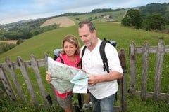 Couples des aînés trimardant dans le beau paysage vert Photos stock