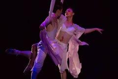 Couples des acrobates accrochant sur un fil Image stock