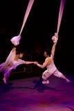 Couples des acrobates accrochant sur un fil Photographie stock libre de droits