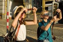 Couples des adolescents avec les négatifs de observation de photo de film d'intérêt et de surprise, fond de rue de ville Photographie stock