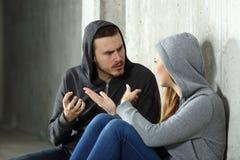 Couples des adolescents discutant dans un endroit foncé Photos stock