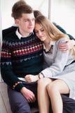 Couples des adolescents s'asseyant contre le mur de miroir Image stock