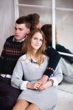 Couples des adolescents s'asseyant contre le mur de miroir Photos stock