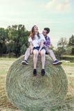 Couples des amants ayant l'amusement dehors sur un coucher du soleil d'été Photos libres de droits