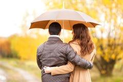 Couples des amants embrassant sous la pluie Image stock