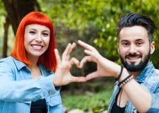 Couples des amants formant un coeur avec leurs mains Images stock