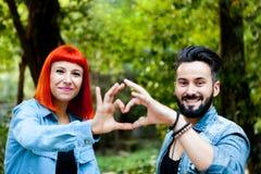 Couples des amants formant un coeur avec leurs mains Photo stock