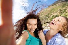 Couples des amies prenant des selfies d'amusement Photos stock