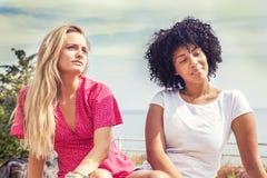 Couples des amies s'asseyant sur un banc Photo libre de droits