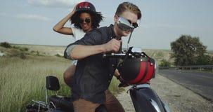 Couples des amis allant sur le tour avec une motocyclette et des casques rouges banque de vidéos