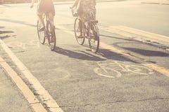 Couples des amis avec des bicyclettes sur la ruelle de vélo Photographie stock libre de droits