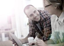 Couples des amis buvant du café et surfant sur l'Internet Photographie stock libre de droits