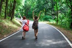 Couples des amis dans une route faisant de l'auto-stop avec le sac à dos et la guitare Photos stock