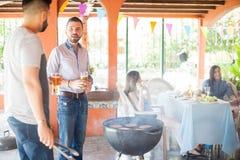 Couples des amis masculins faisant des hamburgers dans un gril Image libre de droits