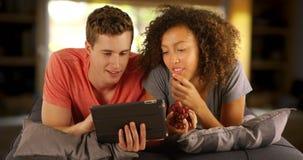 Couples des amis multiraciaux à l'aide du dispositif tenu dans la main de comprimé Images stock