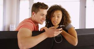 Couples des amis sur les écouteurs de port de divan à écouter la musique Photographie stock libre de droits