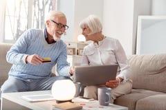 Couples des baby boomers discutant vigoureusement l'achat en ligne photographie stock libre de droits