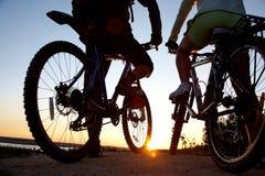 Couples des bicyclettes sur le coucher du soleil Photographie stock libre de droits