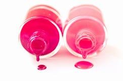 Couples des bouteilles rouges et roses de nailpolish sur le blanc Photographie stock libre de droits
