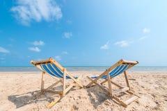 Couples des chaises sur la plage sablonneuse le jour ensoleillé recherchant le bleu photographie stock libre de droits
