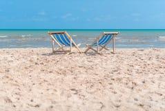 Couples des chaises sur la plage sablonneuse le jour ensoleillé recherchant le bleu images libres de droits
