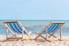 Couples des chaises sur la plage sablonneuse le jour ensoleillé recherchant le bleu image libre de droits