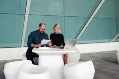 Couples des chefs réussis d'homme et de femme utilisant l'ordinateur portable pour pour trouver de nouveaux travailleurs Image stock