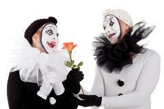 Couples des clowns dans l'amour avec une fleur Photographie stock
