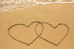 Couples des coeurs dessinés sur le sable de plage dans le jour ensoleillé Amour Photographie stock