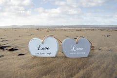 Couples des coeurs en bois inscrits d'amour dans le sable Photos stock