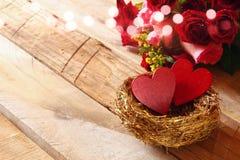 Couples des coeurs rouges dans le nid sur la table en bois Image stock