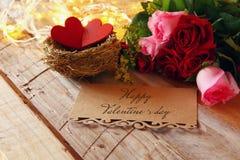 Couples des coeurs rouges dans le nid sur la table en bois Image libre de droits