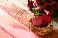 Couples des coeurs rouges dans le nid sur la table en bois Images stock