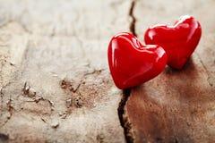 Couples des coeurs rouges sur le bois criqué rugueux Image stock