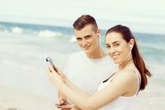 Couples des coureurs avec les téléphones intelligents mobiles dehors Photographie stock libre de droits