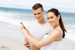 Couples des coureurs avec les téléphones intelligents mobiles dehors Image stock