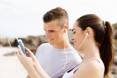 Couples des coureurs avec les téléphones intelligents mobiles dehors Photographie stock