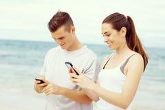 Couples des coureurs avec les téléphones intelligents mobiles dehors Photo libre de droits