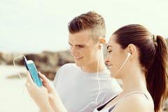 Couples des coureurs avec les téléphones intelligents mobiles dehors Images libres de droits